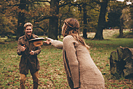 Young couple playing with a hat in an autumnal park - CHAF000209