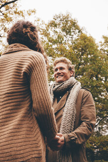 Young couple in love holding hands in an autumnal park - CHAF000219