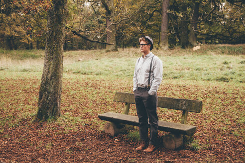 Young man standing in front of a bench in autumnal park looking at distance - CHAF000222
