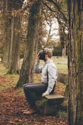 Young man sitting on a bench in autumnal park covering his face with a hat - CHAF000224