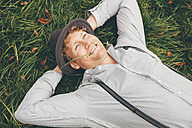 Portrait of smiling young man lying on a meadow with hands behind his head - CHAF000230