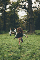 Back view of little girl running in a park while her parents standing in the background - CHAF000243