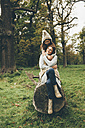 Mother and litte daughter together on a tree trunk in autumnal park - CHAF000252
