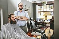 Portrait of smiling barber with customer in barber shop - MADF000345