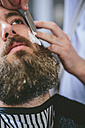 Man with full beard getting a shave at the barber - MADF000350