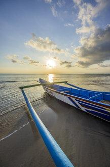 Indonesia, Bali, Jimbaran, Traditional fishing boat on the beach at sunset - THAF001398