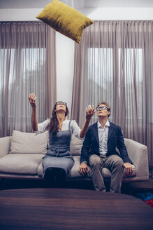 Young couple at home sitting on sofa with cushion flying mid-air - CHAF000304