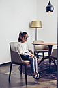 Girl sitting on chair with oversized glasses - CHAF000310