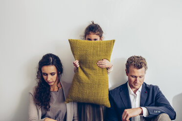 Couple having relationship conflict with their daughter hiding her face behind cushion - CHAF000323
