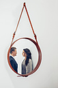 Reflection of couple in a mirror hanging on wall - CHAF000326