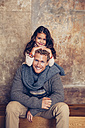 Portrait of smiling father sitting on wooden bench with daughter - CHAF000338