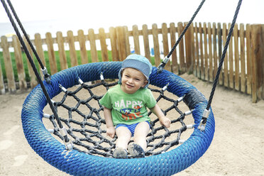 Spain, Majorca, Alcudia, toddler sitting on a swing - GDF000763