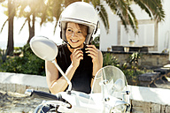Spain, Majorca, Alcudia, portrait of smiling young woman with motor scooter - GDF000779