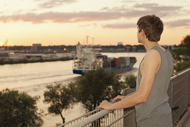 Germany, Hamburg, teenage boy  watching cargoships - MEMF000810