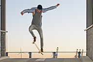 Germany, Hamburg, teenage boy jumping with skateboard on a parkdeck ramp - MEMF000812