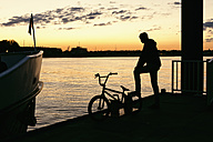 Germany, Hamburg, silhouette of a young man with bike on a jetty at evening light - MEMF000816