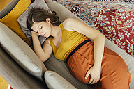 Pregnant woman taking a nap on her couch at home - MFF001790