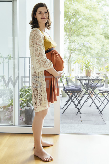 Portrait of pregnant woman holding her belly at home - MFF001795