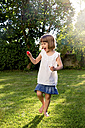 Little girl playing with soap bubbles in a garden - LVF003635