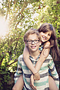 Boy giving his sister a piggy back in the garden - LVF003619