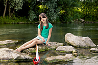 Girl playing with wooden toy boat at a river - LVF003625