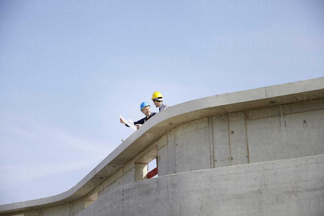 Two men on construction site discussing construction plan - FMKF001586 - Jo Kirchherr/Westend61