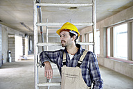 Man with hard hat on construction site thinking - FMKF001597