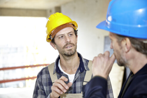Construction worker and architect on construction site discussing - FMKF001600