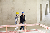Construction worker and architect talking on construction site - FMKF001606
