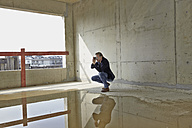 Man taking picture on construction site in unfinished building - FMKF001622