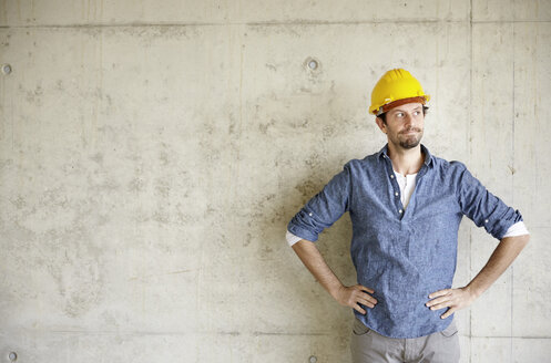 Man with hard hat at concrete wall thinking - FMKF001628
