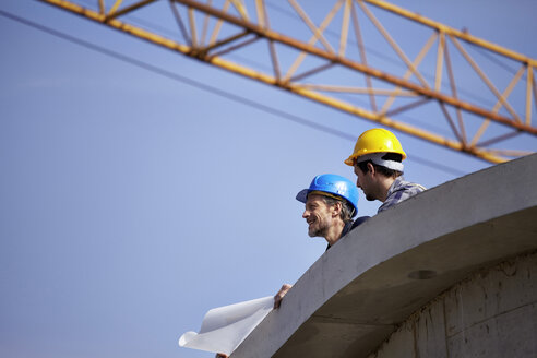 Two men on construction site with construction plan - FMKF001724