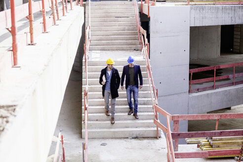 Two men on construction site walking down stairs - FMKF001661