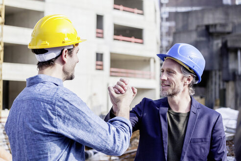 Two men on construction site shaking hands - FMKF001667