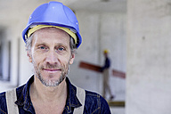Smiling worker on construction site - FMKF001678
