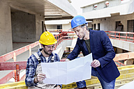 Construction worker and architect with plan talking on construction site - FMKF001685