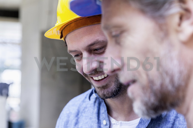 Close-up of two smiling men on construction site - FMKF001688