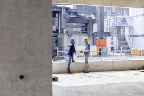 Two men with hard hats talking on construction site - FMKF001691