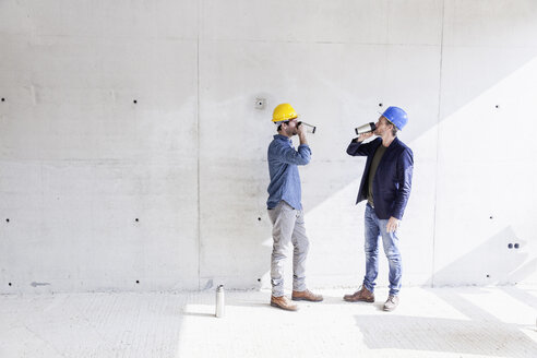 Two men on construction site drinking from mugs - FMKF001697