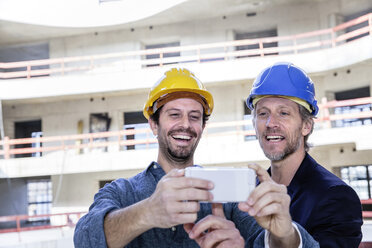 Two happy men on construction looking at cell phone - FMKF001699