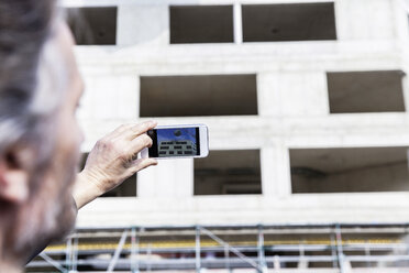 Man taking picture on construction site - FMKF001702