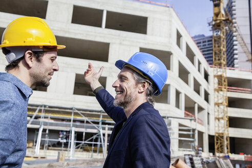 Two men on construction site wearing hard hats - FMKF001705
