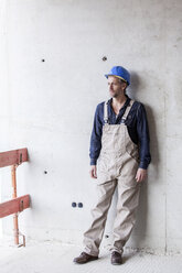 Worker on construction site standing at concrete wall - FMKF001708