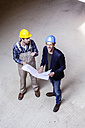 Construction worker and architect with plan talking on construction site - FMKF001845