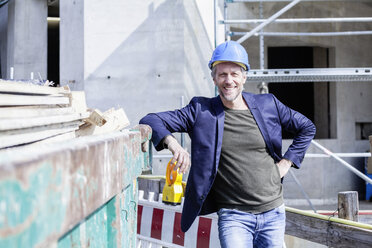 Smiling architect on construction site - FMKF001713