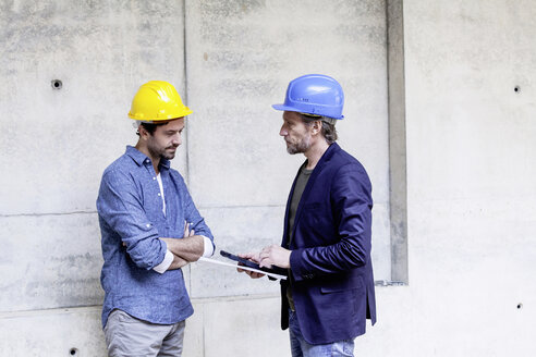 Two men on construction site wearing hard hats - FMKF001733