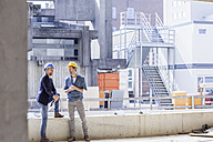 Two men on construction site wearing hard hats - FMKF001717