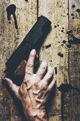 Man's hand, revolver and cartridges on wood - MID000480