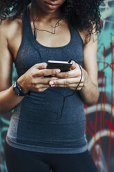 Young woman holding smartphone hearing music with earphones, close-up - EBSF000750