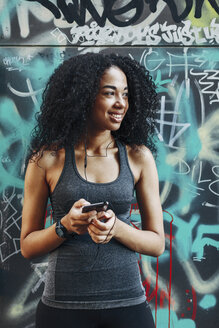Young woman holding smartphone hearing music with earphones - EBSF000752